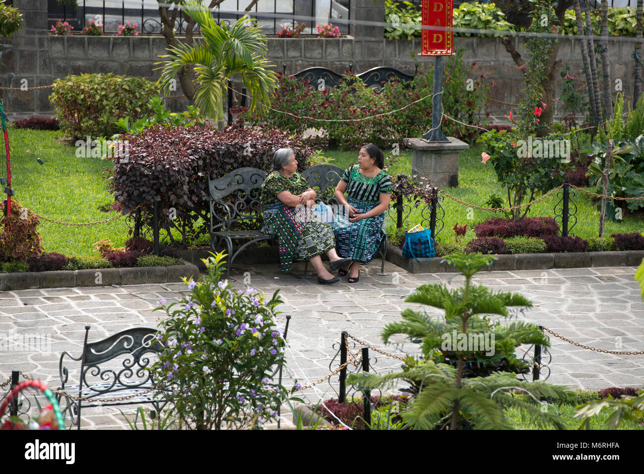 Two indigenous, ethnic Tz'utujil Maya women sitting on a park bench, talking in Santiago de Atitlán, Sololá Department, Stock Photo