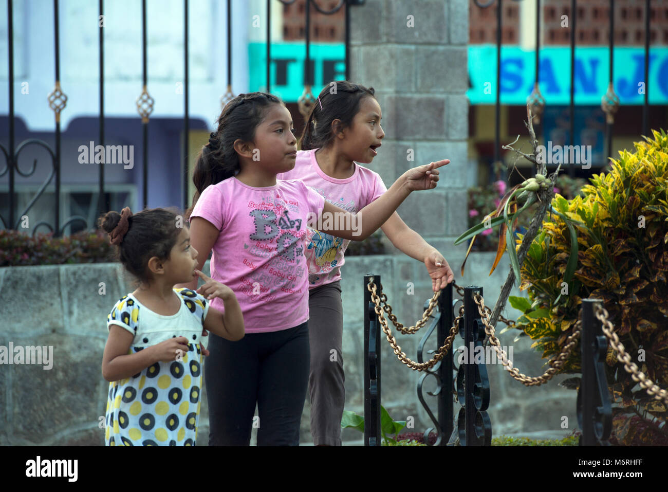 Indigenous, ethnic Tz'utujil Mayan girls walking though a park in modern clothes in Santiago de Atitlán, - Stock Image