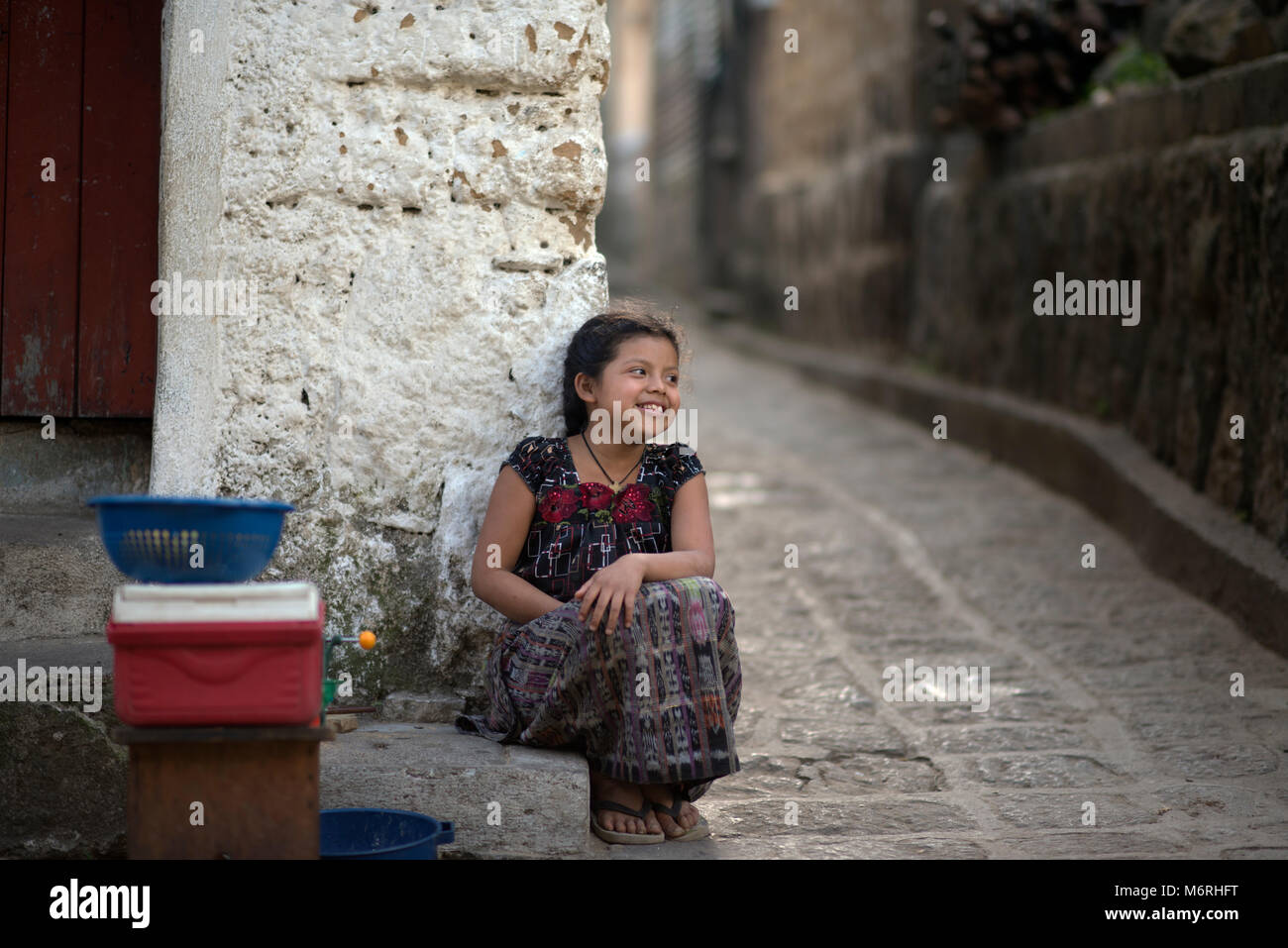 A young indigenous, ethnic Tz'utujil Mayan girl in traditional clothes sitting outside her house. Santiago de - Stock Image