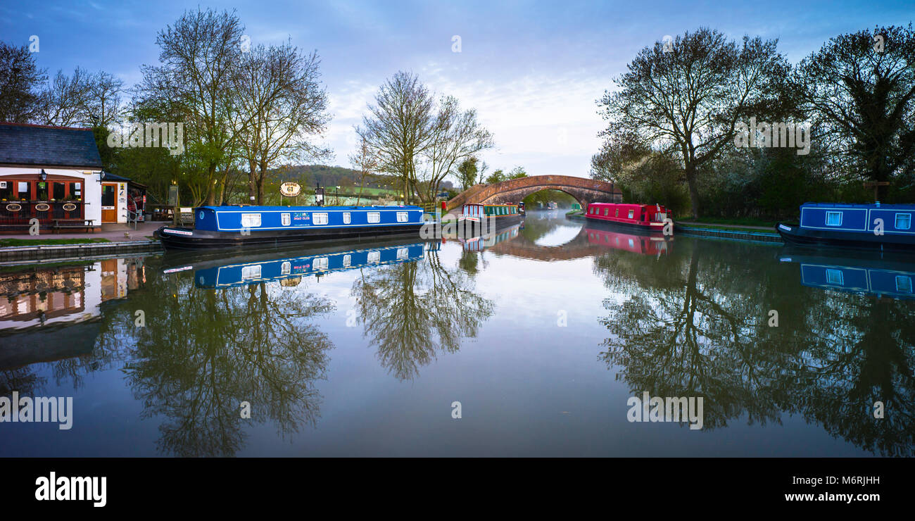 Canal basin on the Grand Union canal showing one of the pubs,several narrowboats and a hump backed bridge. - Stock Image