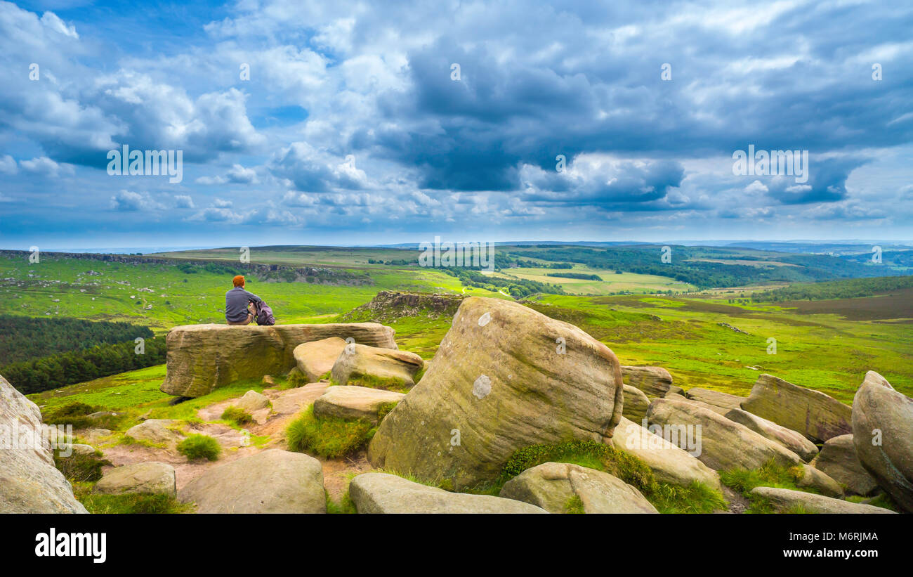 A rambler on Higger Tor in the Derbyshire Peak District with Carl Wark in the middle distance. - Stock Image