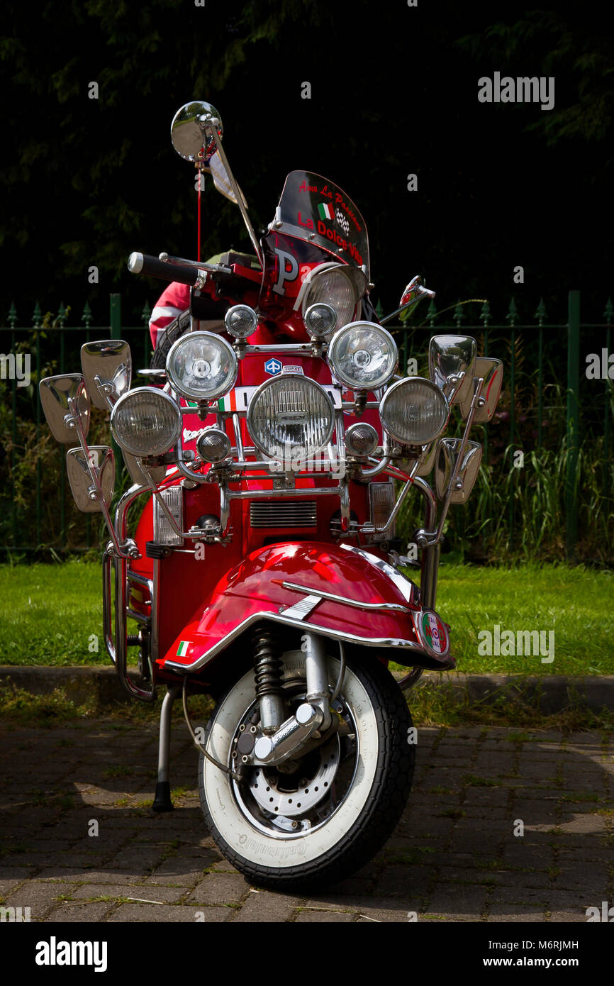 A red scooter with many lights and mirrors in the style of a mod's scooter from the 1960's. - Stock Image