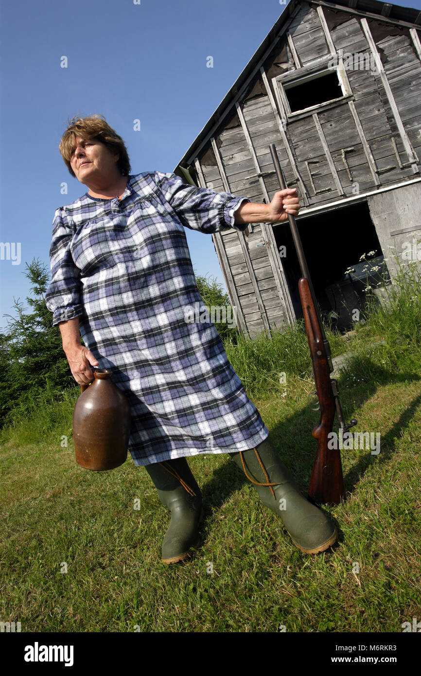 Moonshine Mary stands proud protecting her moonshine with a rather large shotgun. - Stock Image
