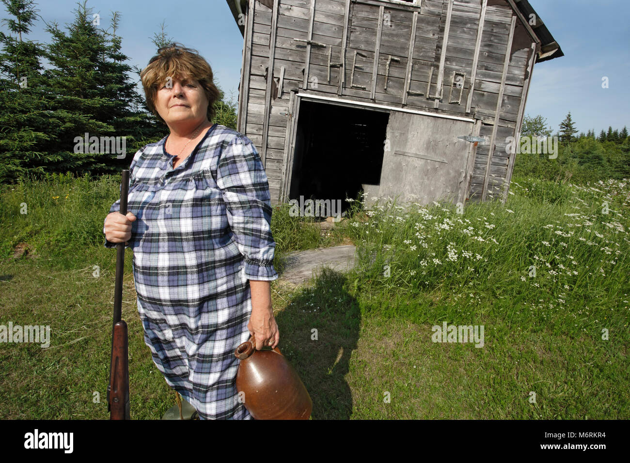 Moonshine Mary stands proud protecting her property and moonshine with a rather large rifle. - Stock Image