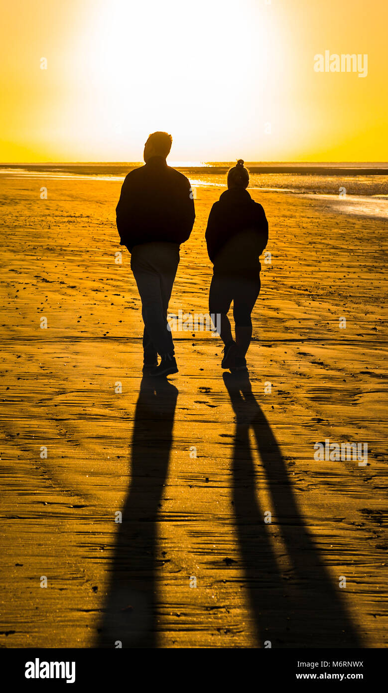 Couple of people walking on a sandy beach in the morning towards the rising sun, which casts long shadows. - Stock Image