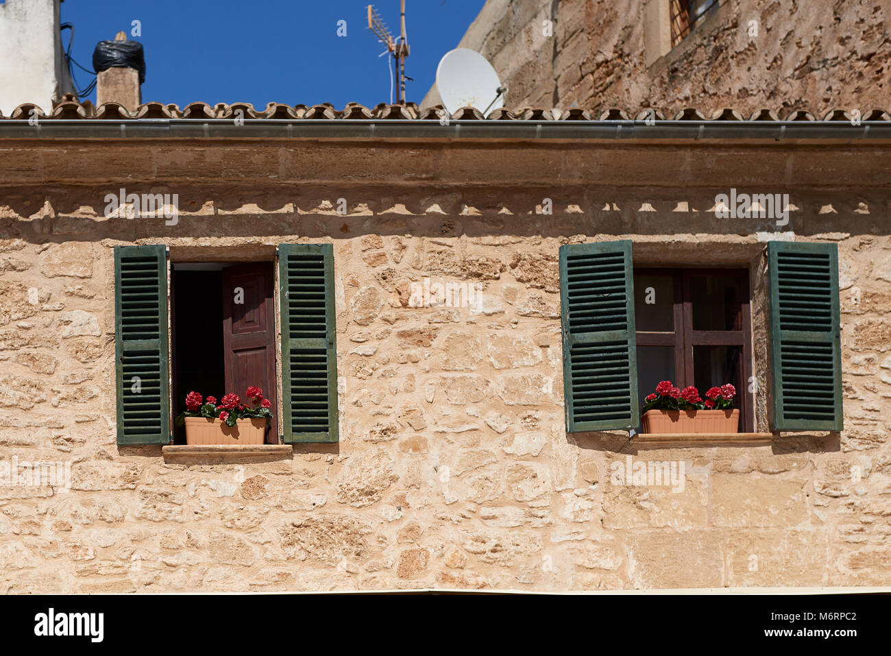 Window Boxes With Colorful Flowers In The Open Windows Of An Old Apartment  Or House With