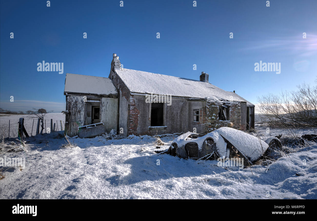 Abandones derelict cottage and car in remote countryside location. - Stock Image