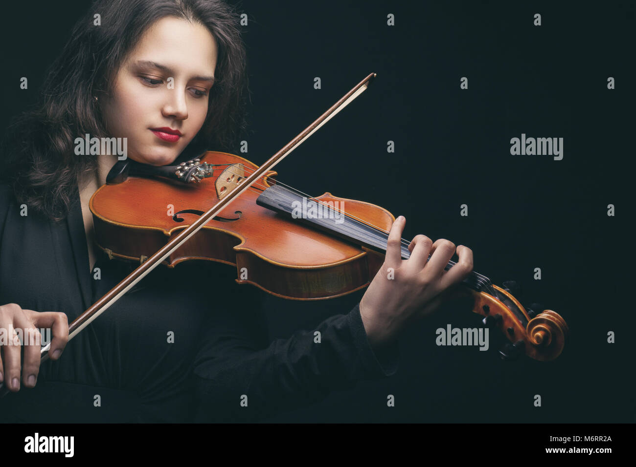 Beautiful young woman playing the violin on dark background - Stock Image