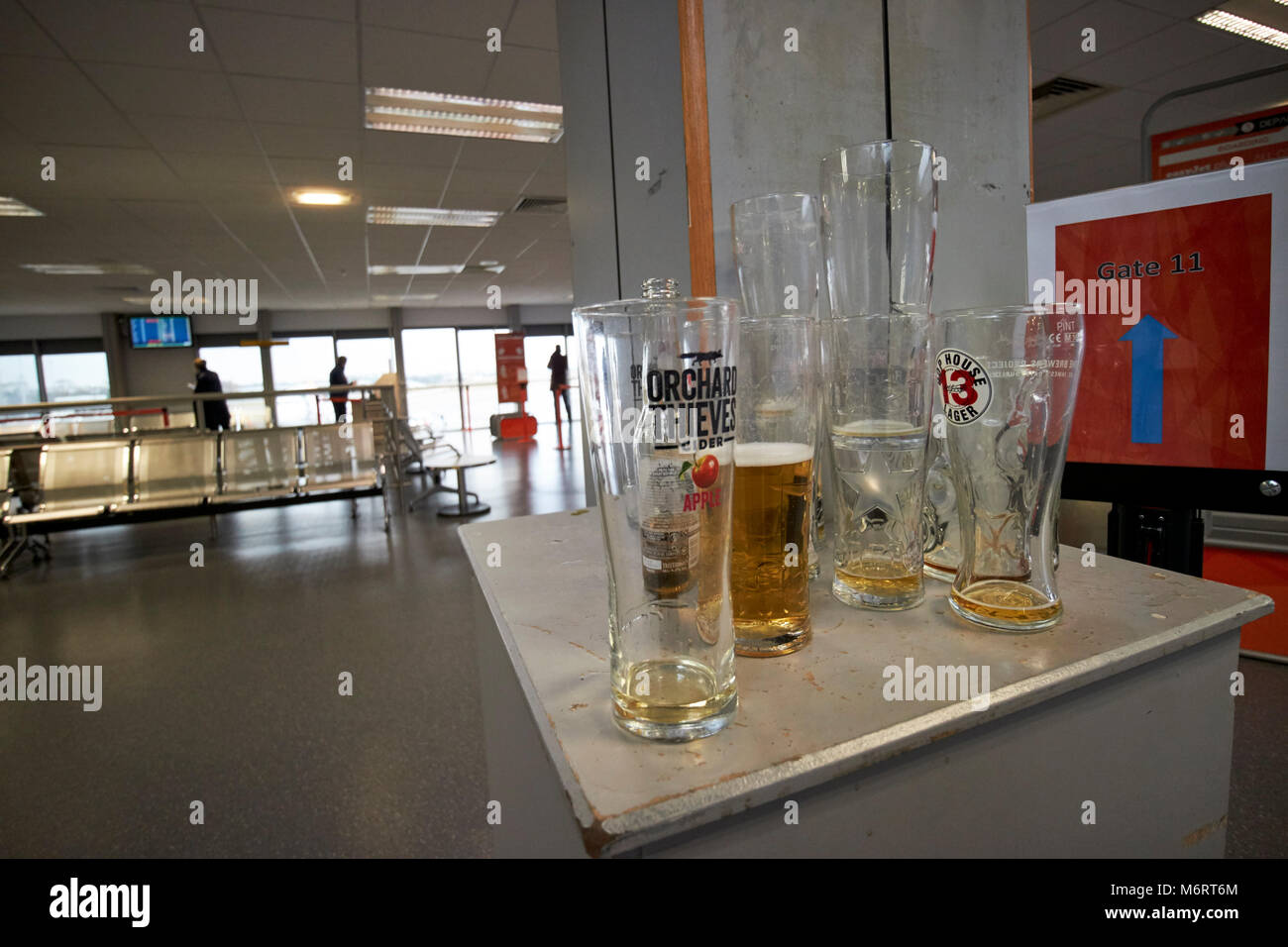 empty and half finished pints of alcohol left at an airport departure lounge before boarding plane in the uk - Stock Image