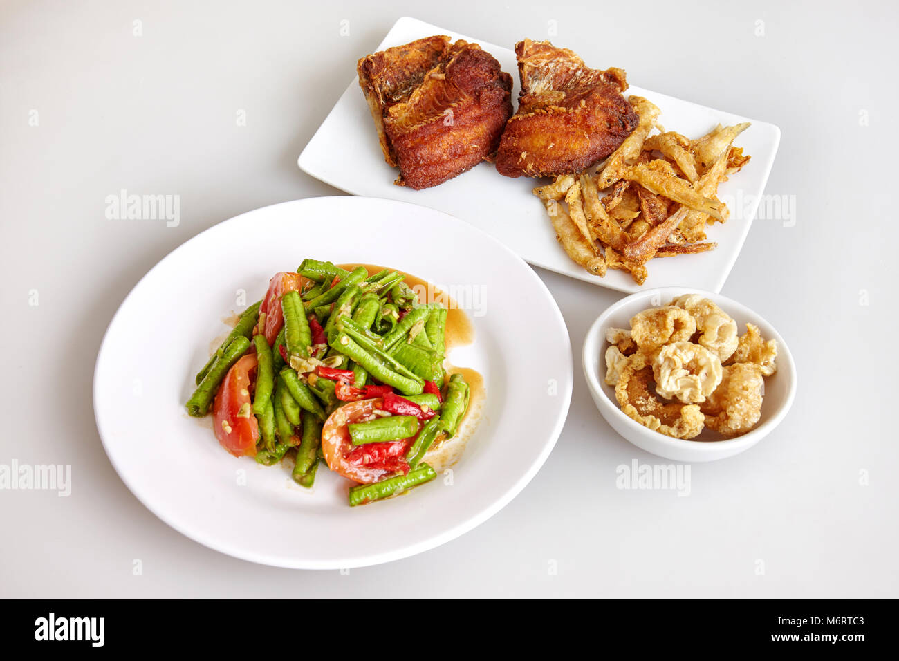 Thai traditional food, local food, long beans spicy salad (cow pea), Crispy pork skin and crisp tilapia fish fried - Stock Image