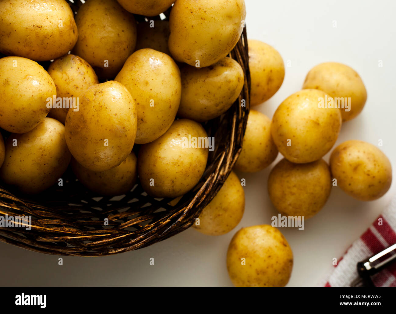 Within a wicker basket are several pounds of New Potatoes with peeler at side Stock Photo