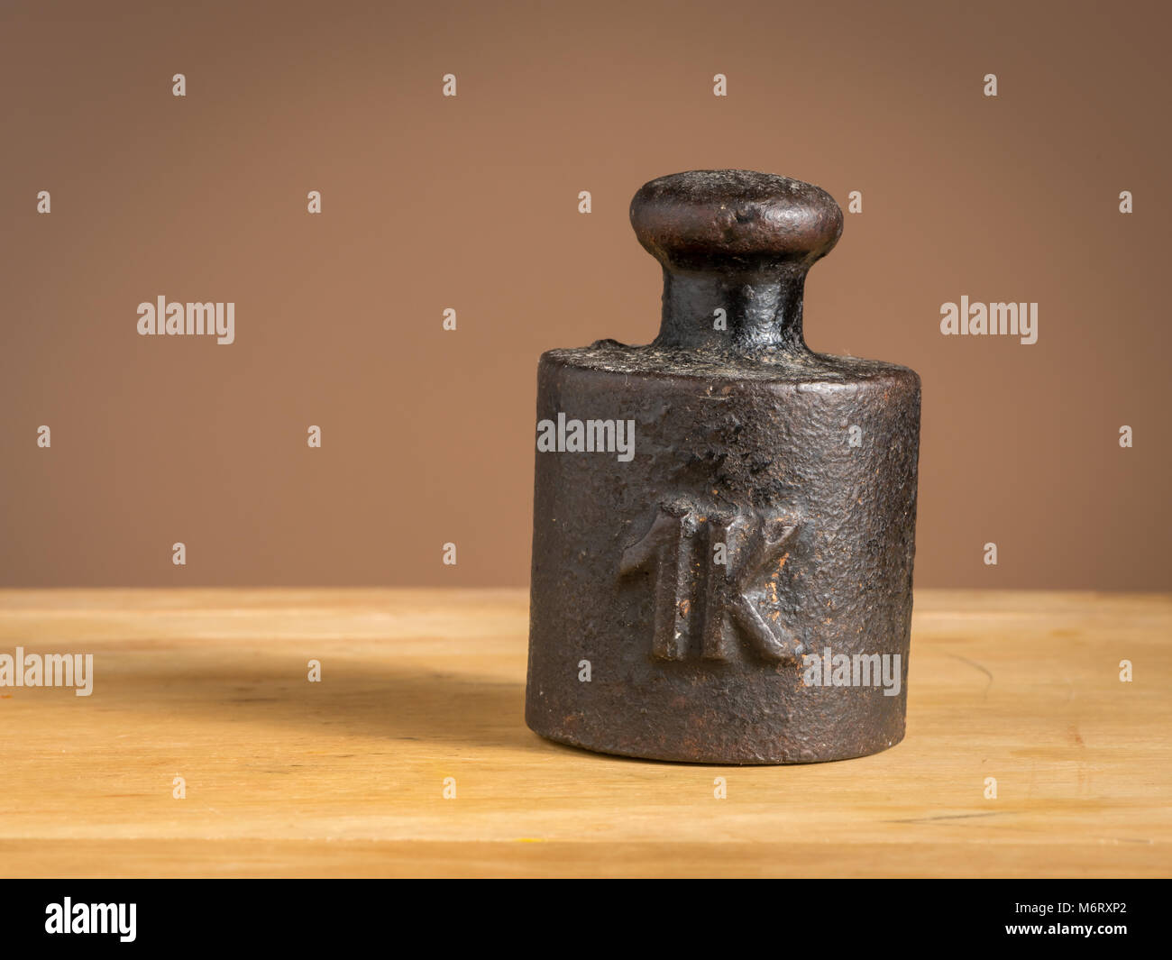 Old black iron 1kg weight for a kitchen scale standing on a table - Stock Image