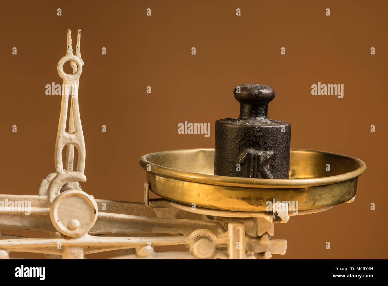 Old white vintage kitchen scale, brass with weights, brown background - Stock Image