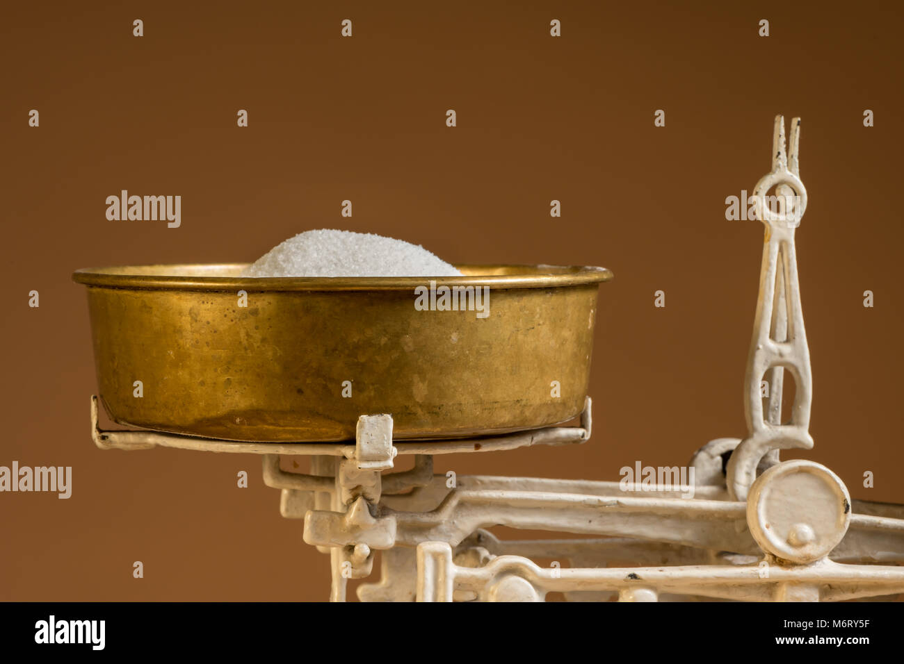 Old white vintage kitchen scale, brass with sugar, brown background - Stock Image