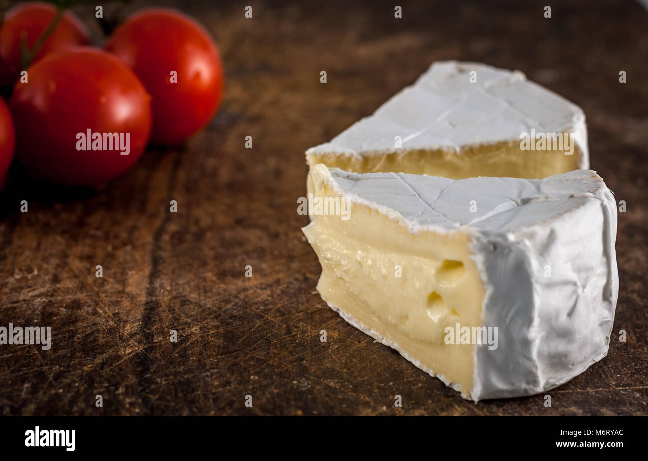 Closeup of brie cheese and cherry tomatoes on wooden chopping board - Stock Image