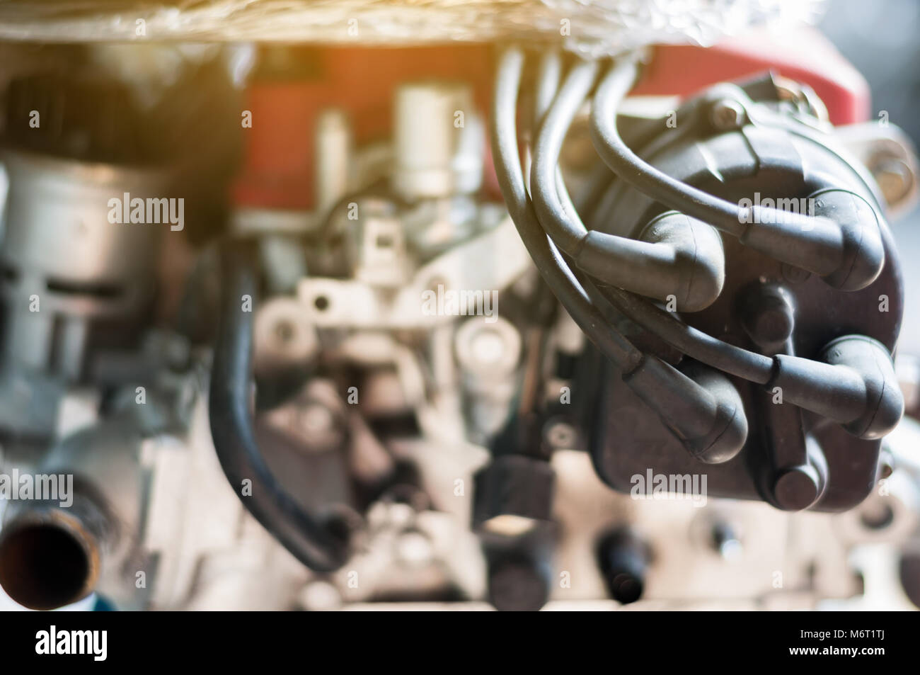 Close up coil distributor wire four cylinder engine stand on car with  sunlight - Stock Image