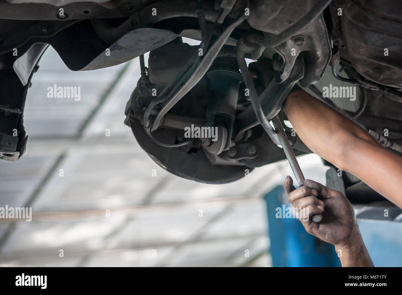 Auto mechanic asian checking bush-bolt under double wishbone suspension by hand with tools car lift - Stock Image