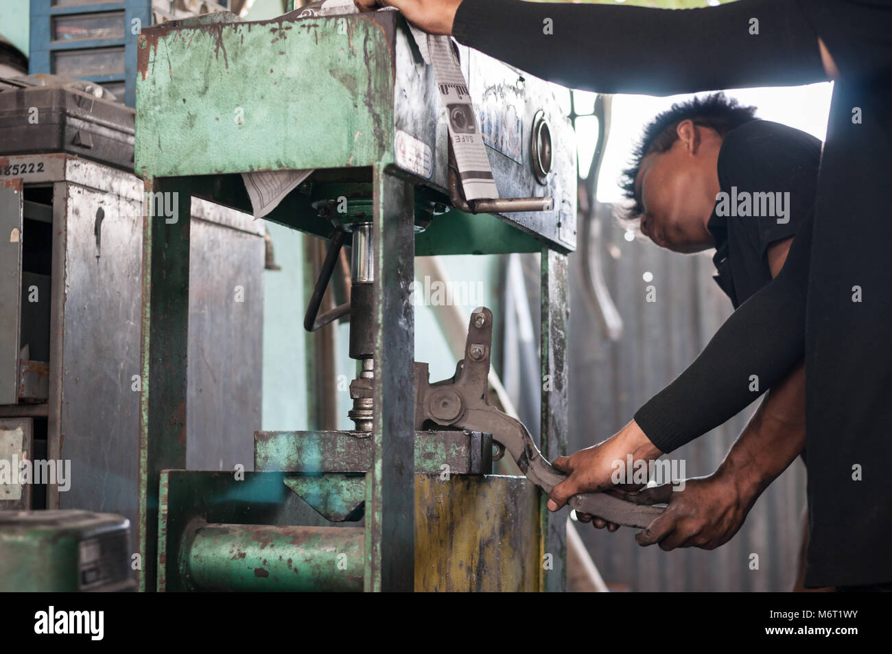 Close up machine compress bush car maintenance with asian mechanic automotive - Stock Image