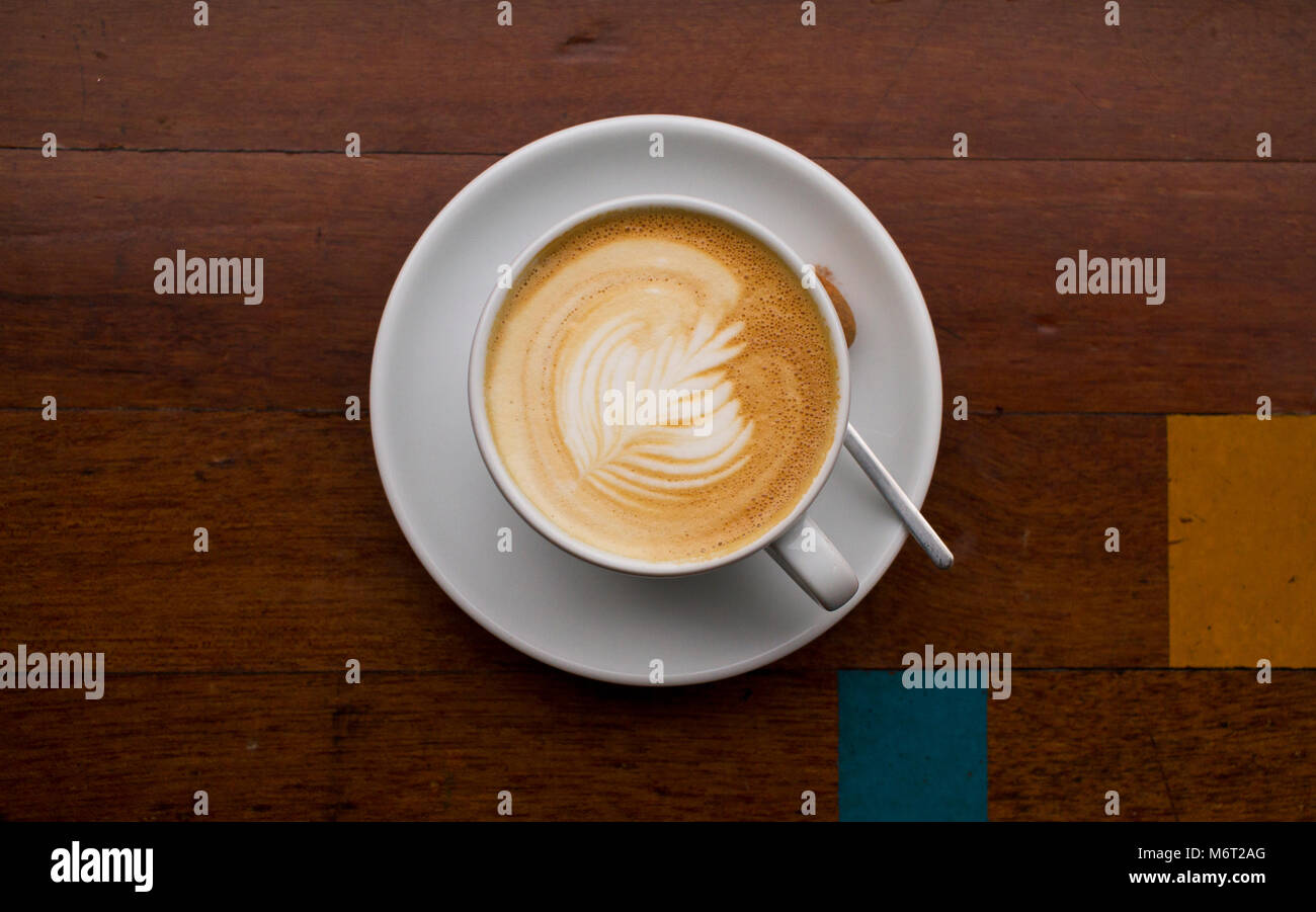 Latte art on a wooden geometric coffee table with a blue and yellow square detail - Stock Image