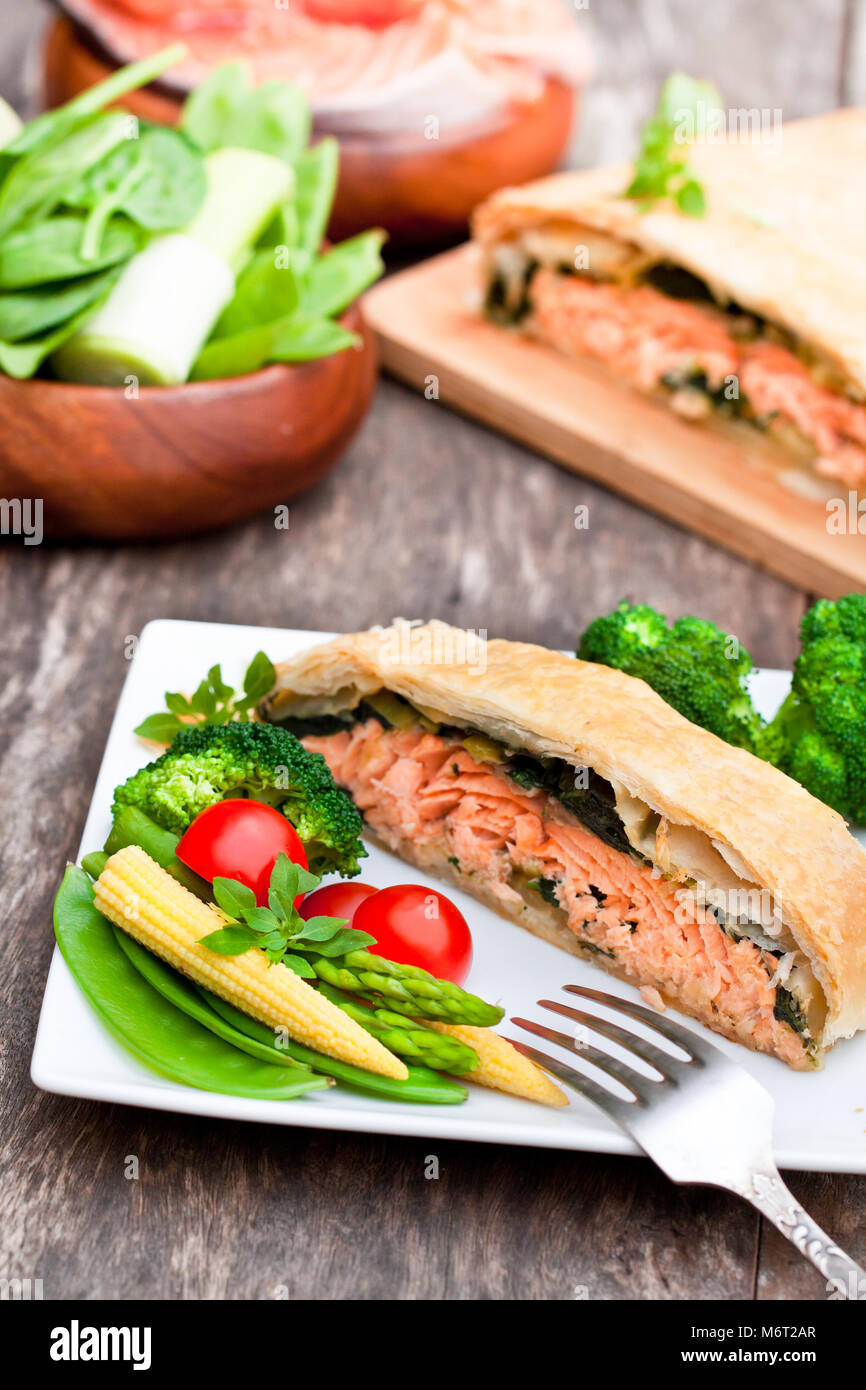 Salmon  fillet on leek and spinachbaked in puff pastry with vegetables Stock Photo