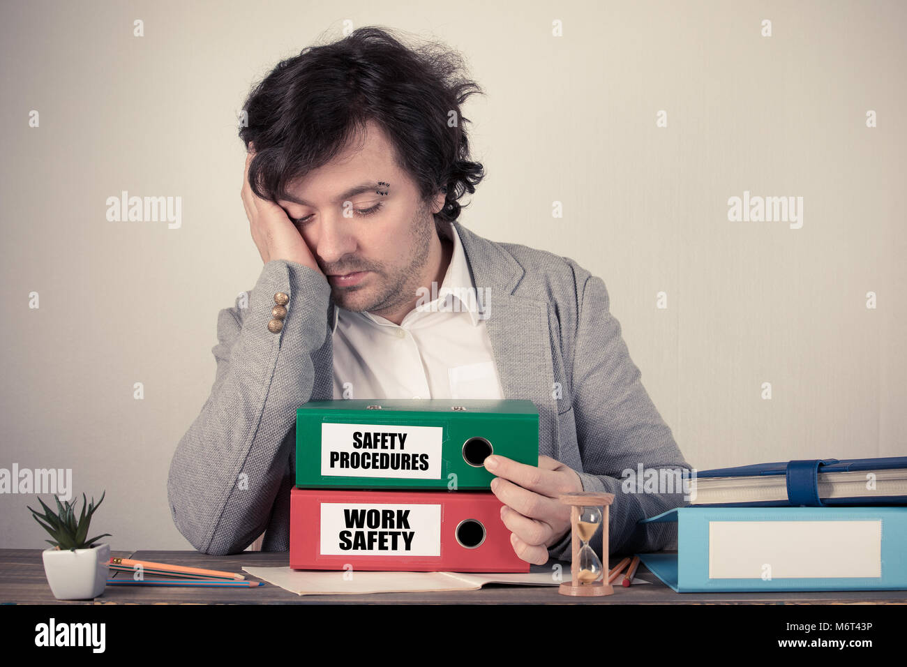 Work Safety and Safety Procedures text on the binders, worried bussinesman thinking by the work desk - Stock Image