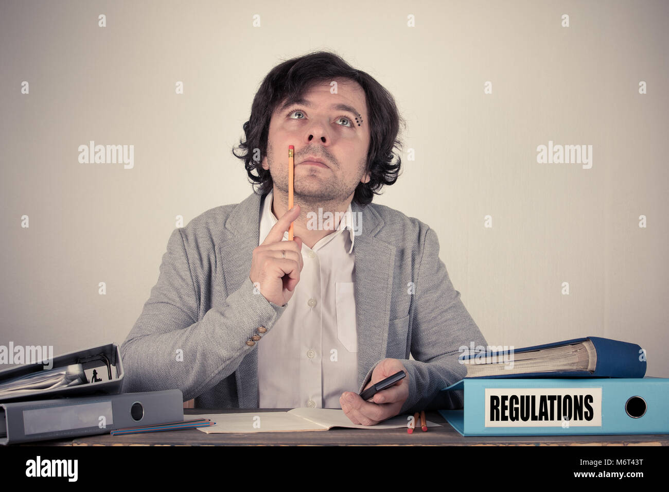 Regulations text on the binder, worried bussinesman thinking by the work desk - Stock Image