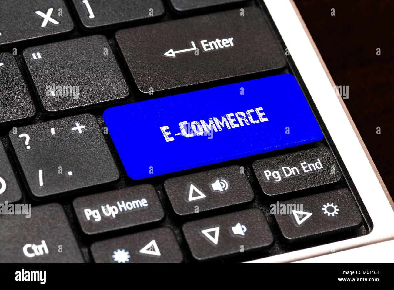 Business Concept - Blue E-Commerce Button on Slim. - Stock Image