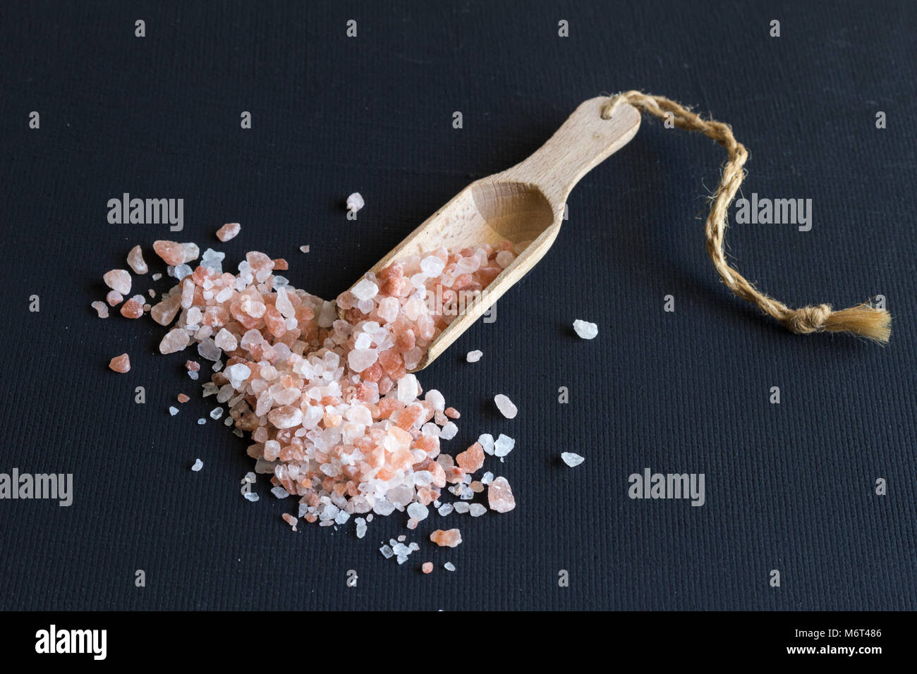 Himalayan rock salt and wooden scoop close up on black rustic background - Stock Image