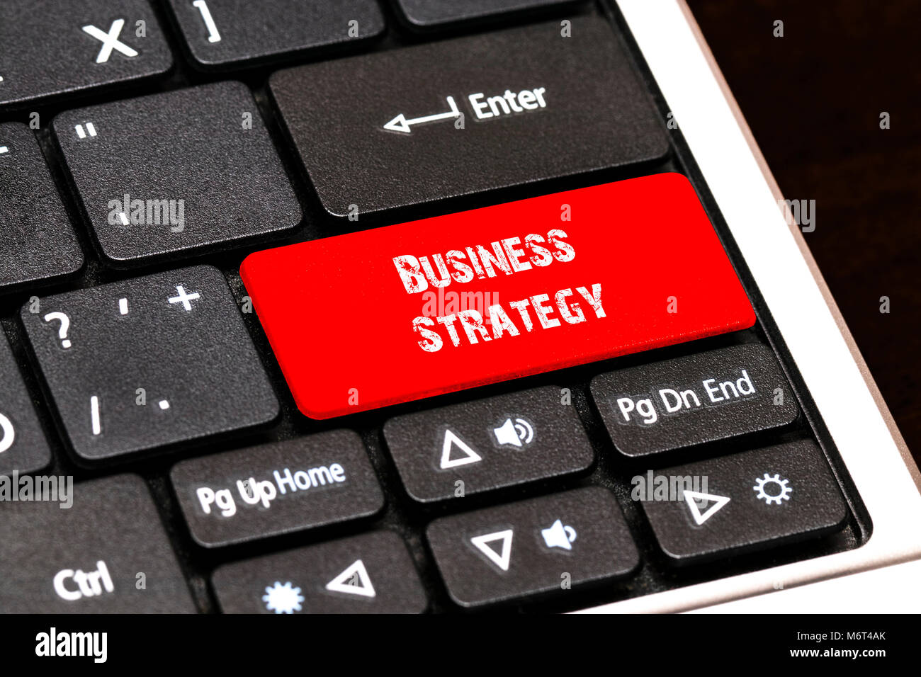 On the laptop keyboard the red button written Business Strategy. - Stock Image