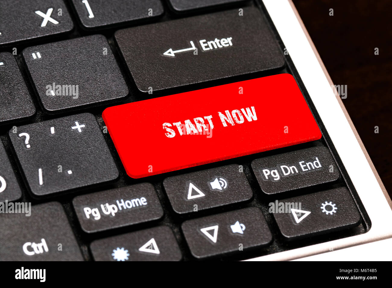 On the laptop keyboard the red button written Start Now. - Stock Image