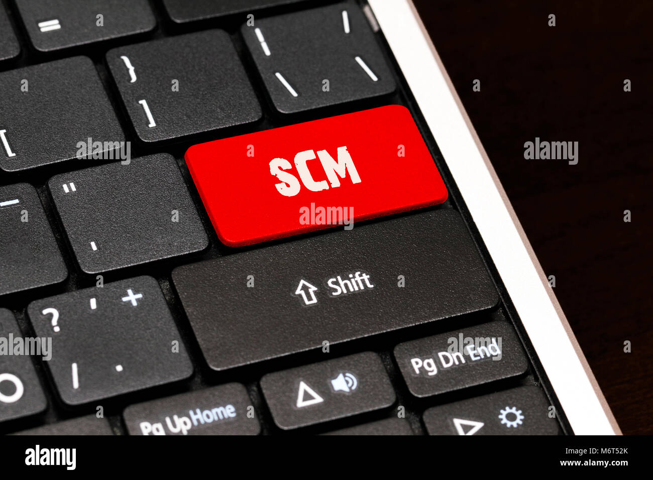 SCM on Red Enter Button on black keyboard. Stock Photo