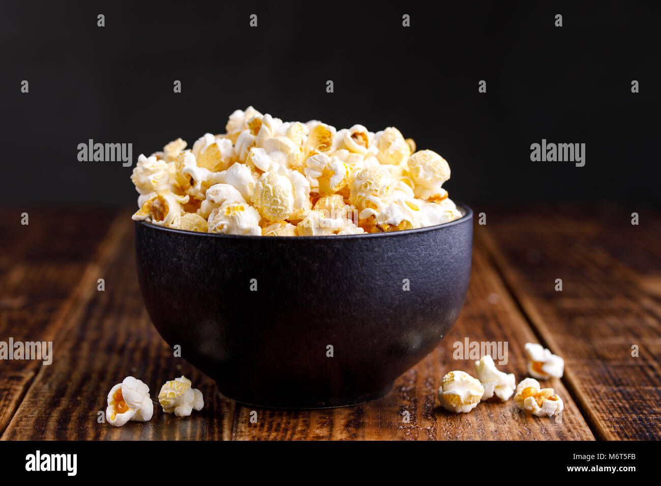 A bowl with popcorn on a wooden background. - Stock Image
