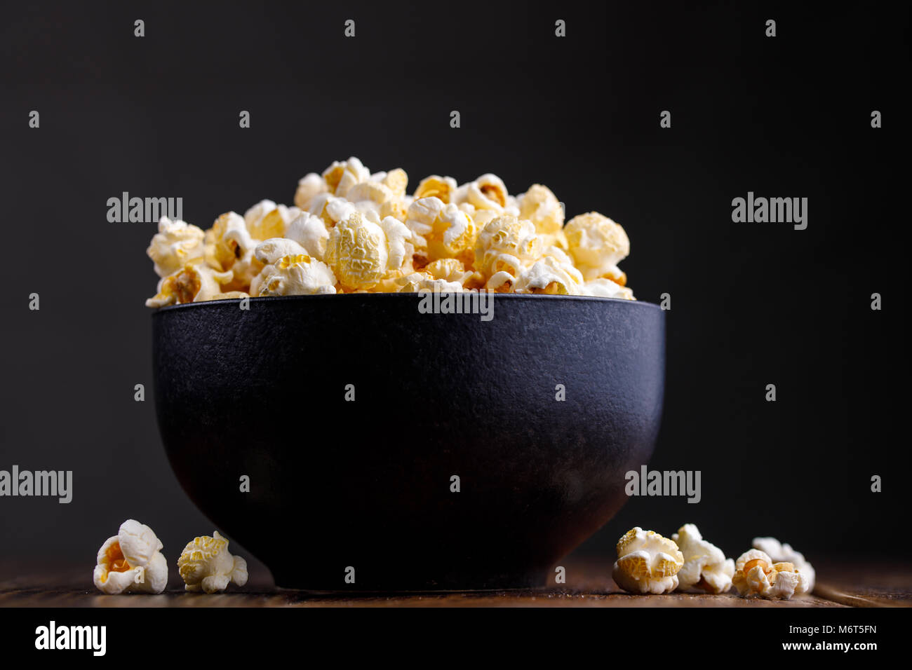 Popcorn in a ceramic bowl on a wooden background. - Stock Image