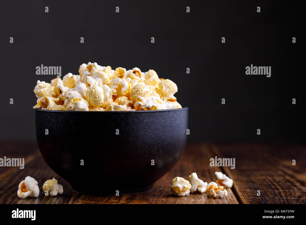 Popcorn in a ceramic bowl and scattered on a wooden background. - Stock Image