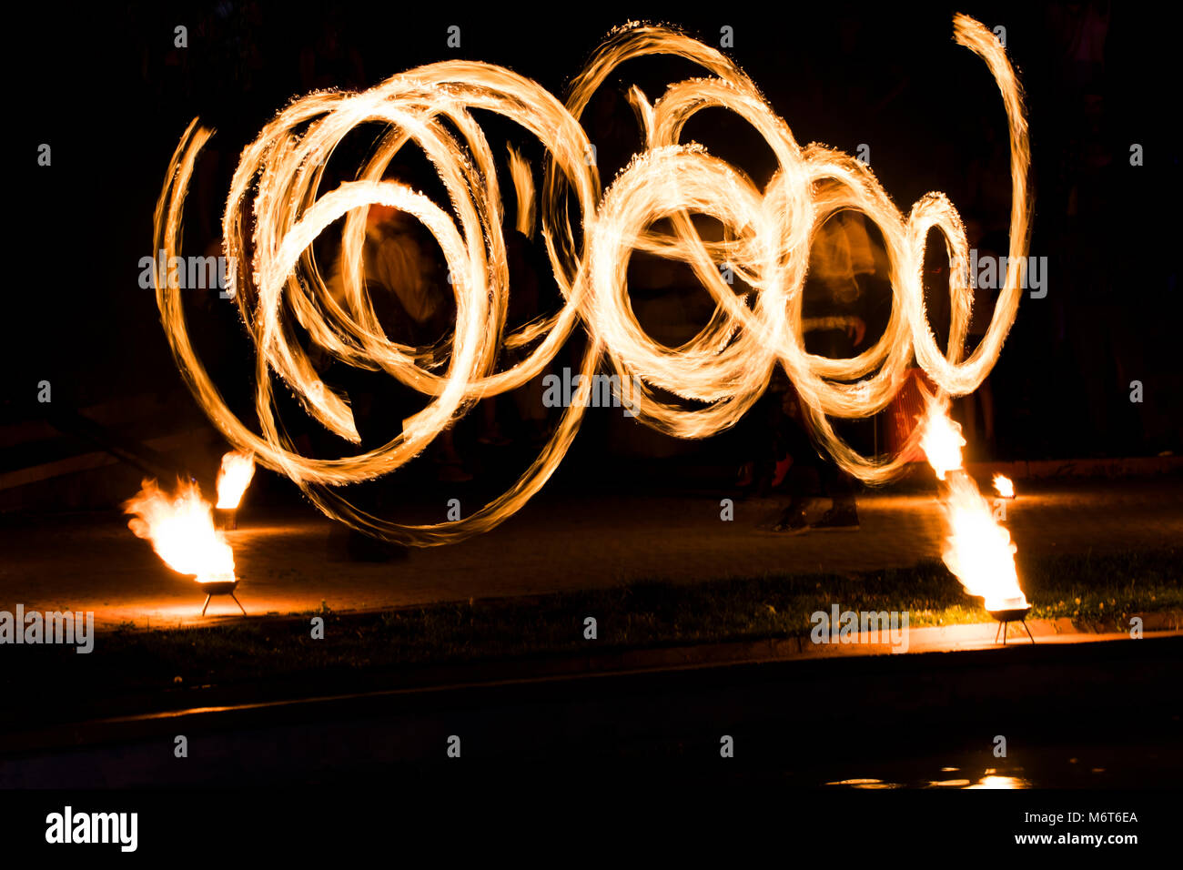 fire show and a lot of the bright sparks in the night. - Stock Image
