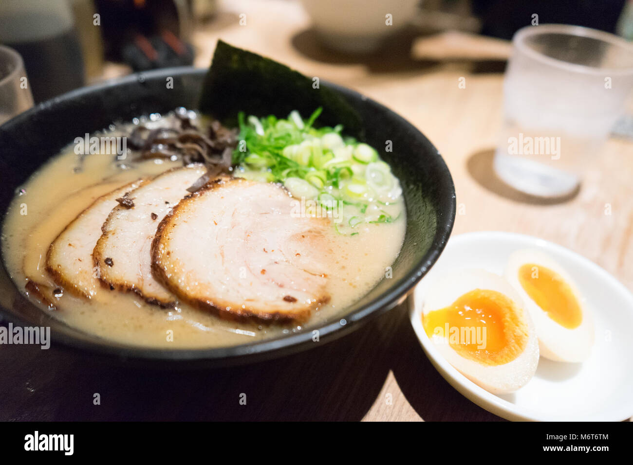 Traditional Japanese soup ramen with meat broth, asian noodles, seaweed, sliced pork, eggs and pickled ginger. Background. - Stock Image
