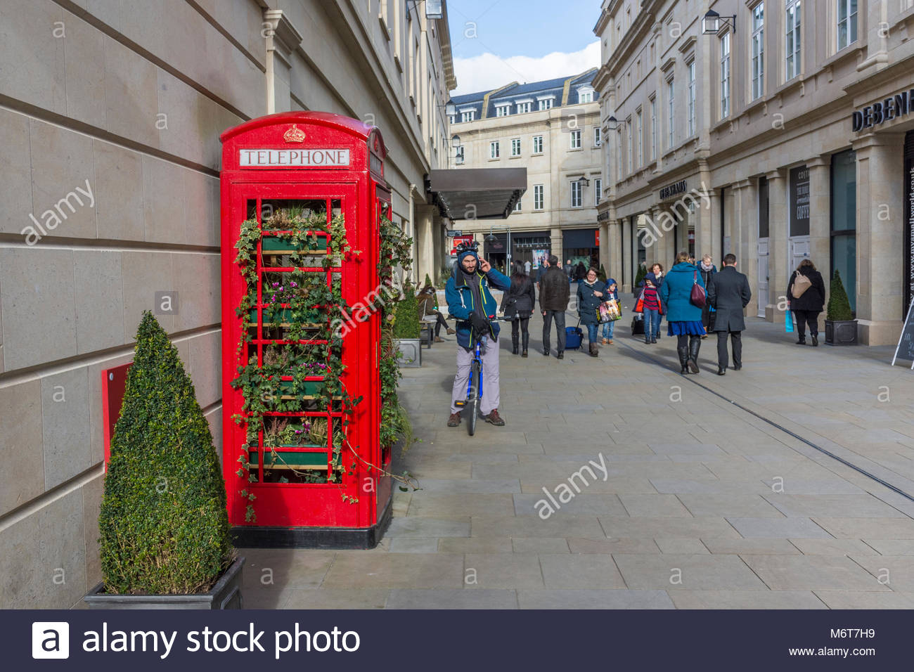 Traditional red telephone box decorated with plants in the SouthGate Shopping precinct - Stock Image