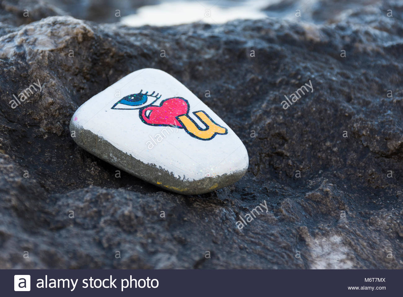 A painted stone with a 'i love you' message left  on a rock as part of a stone hunting game popular with - Stock Image
