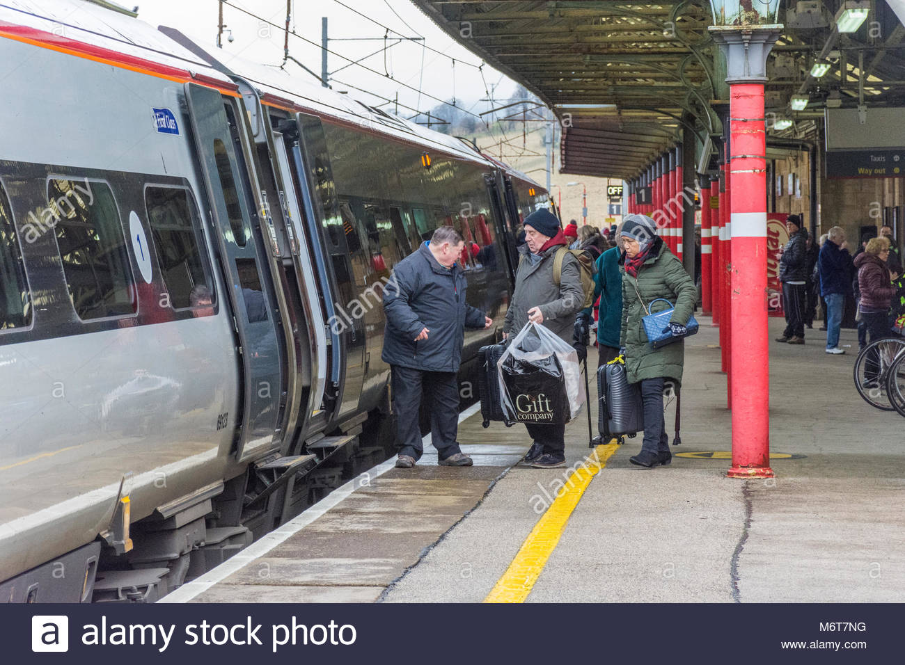 Passengers board a Virgin Train heading south on the West Coast Main line at Oxenholme Station near Kendal, Cumbria - Stock Image