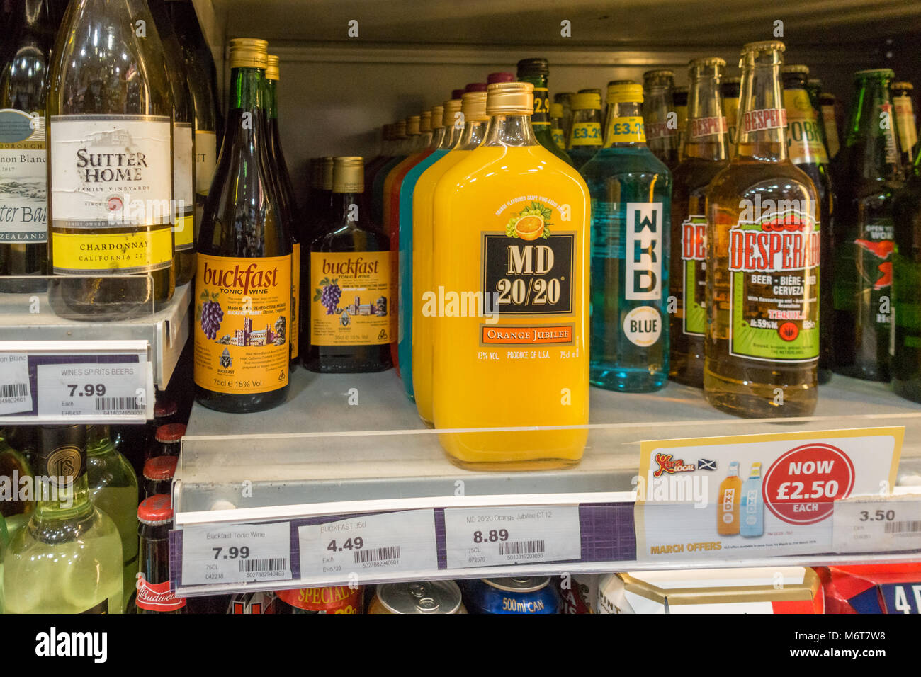 Alcohol, including bottles of Buckfast, MD 50/50 and WKD on sale in off licence in Glasgow, Scotland, UK - Stock Image