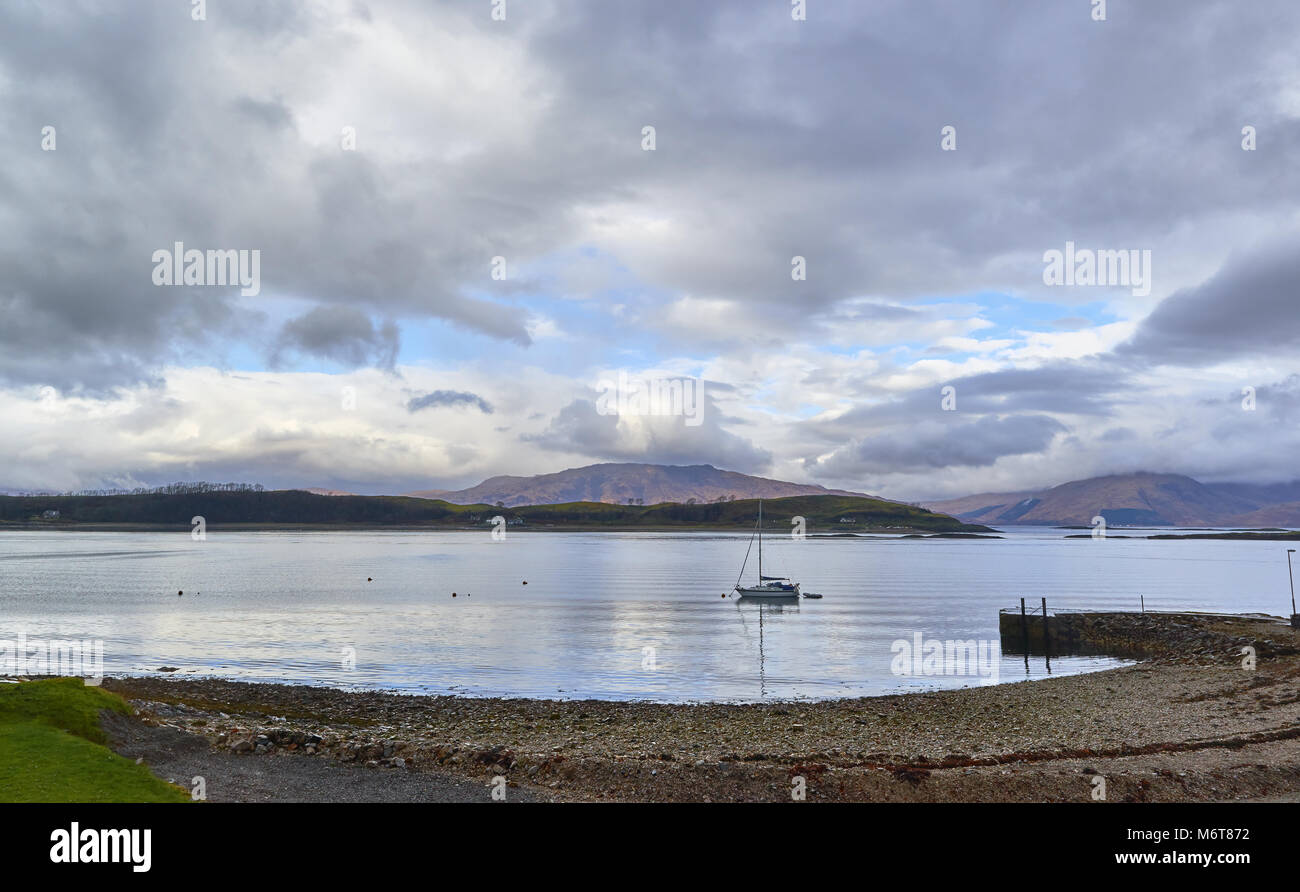 The View North from Port Appin looking towards the Isle of Lismore and the Mountains beyond. A Yacht lies moored - Stock Image