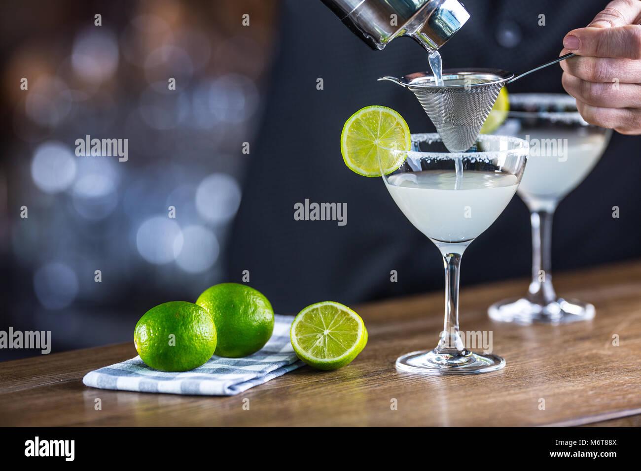 Margarita. Margatita alcoholic cocktail drink on barcounter in pub or restaurant. Barman preparing a cocktail drink. - Stock Image