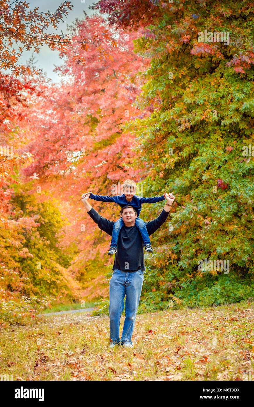 Father giving son piggyback ride in the autumn park - Stock Image
