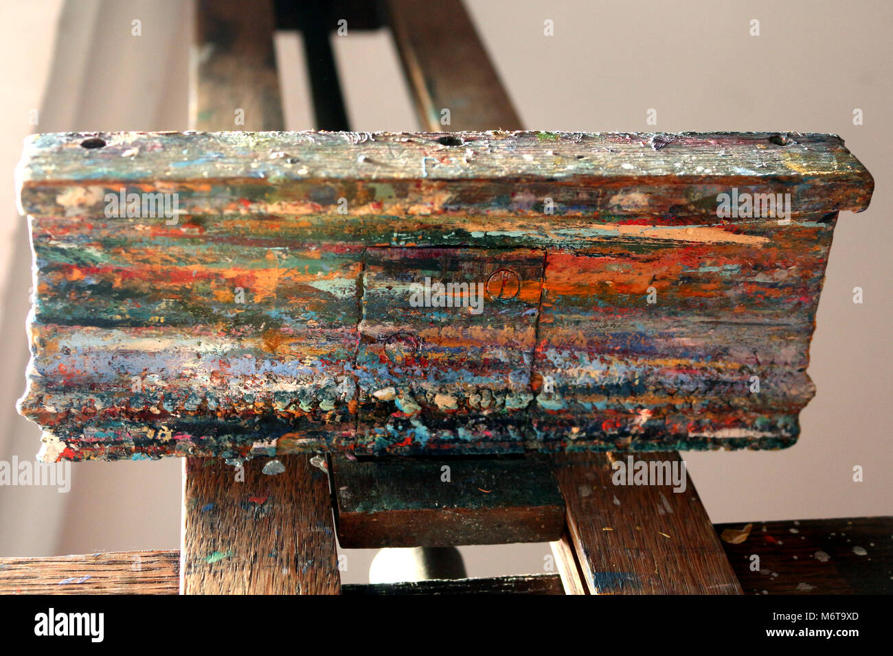 Artists easel spattered with paint after decades of work - Stock Image