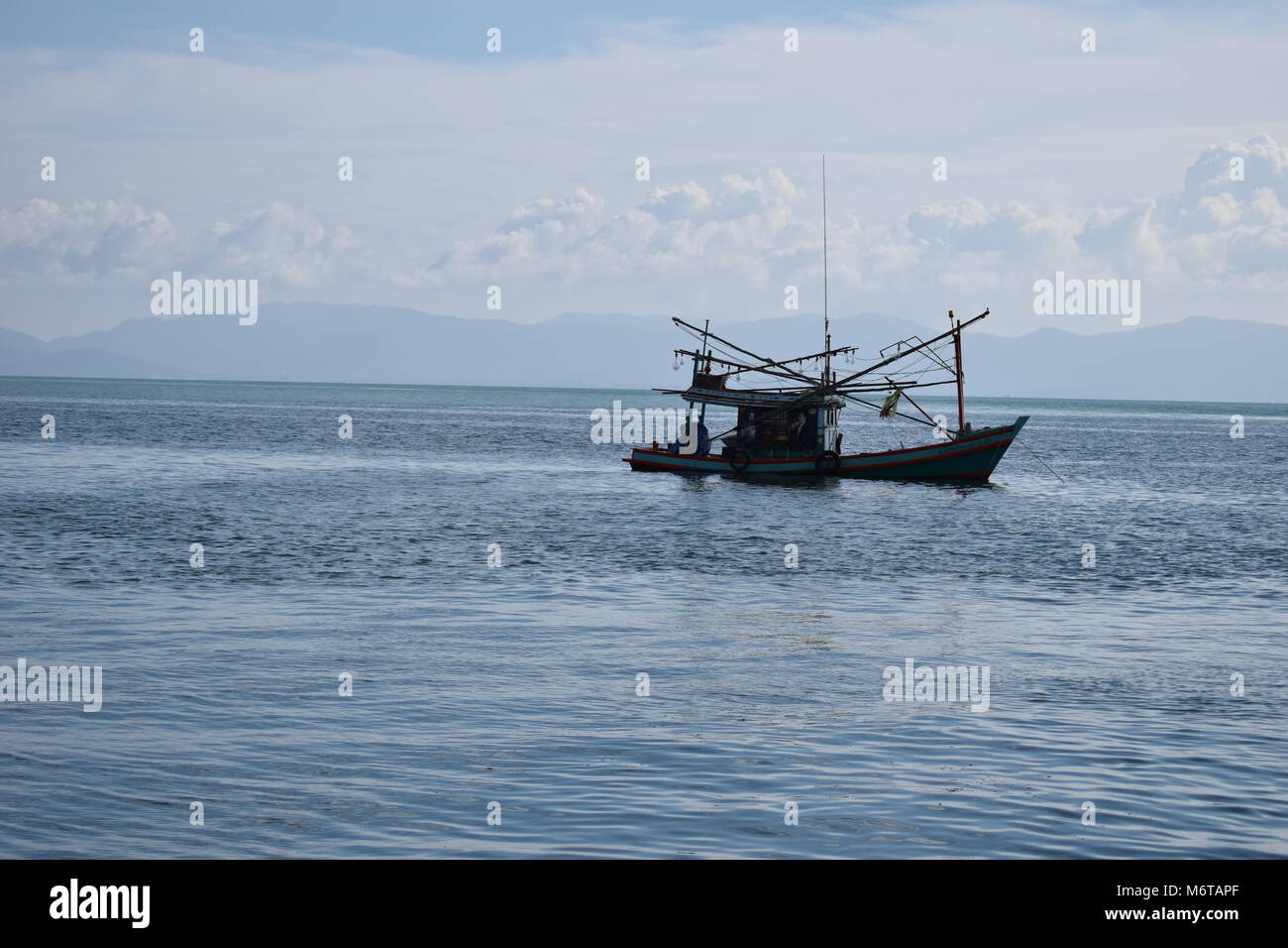 An isolated small fisherman boat in the gulf of Thailand not far from Koh Tao on a clear sea with mountains and - Stock Image