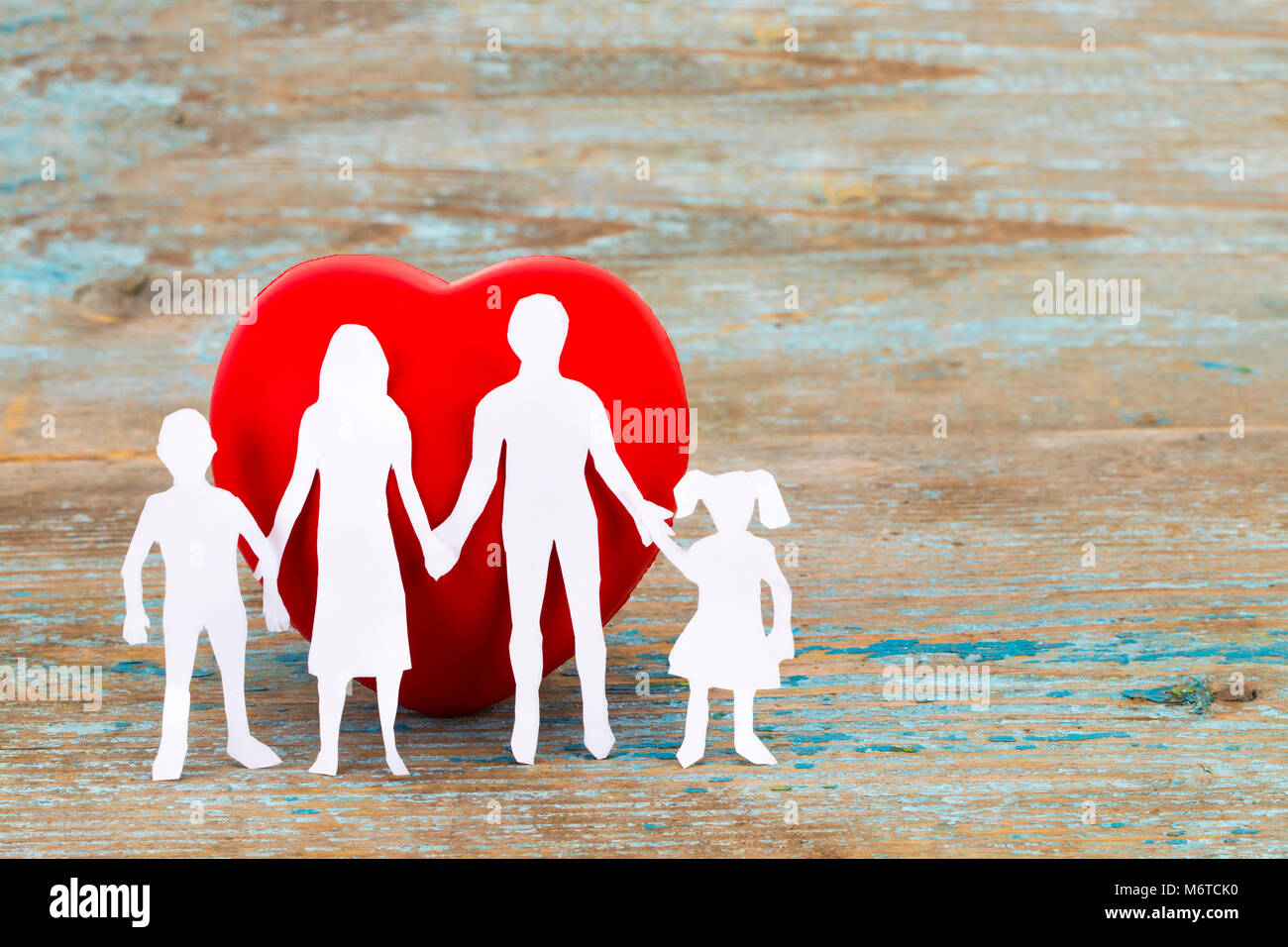Paper silhouette of family and heart on wooden background. Health insurance concept with copy space. - Stock Image