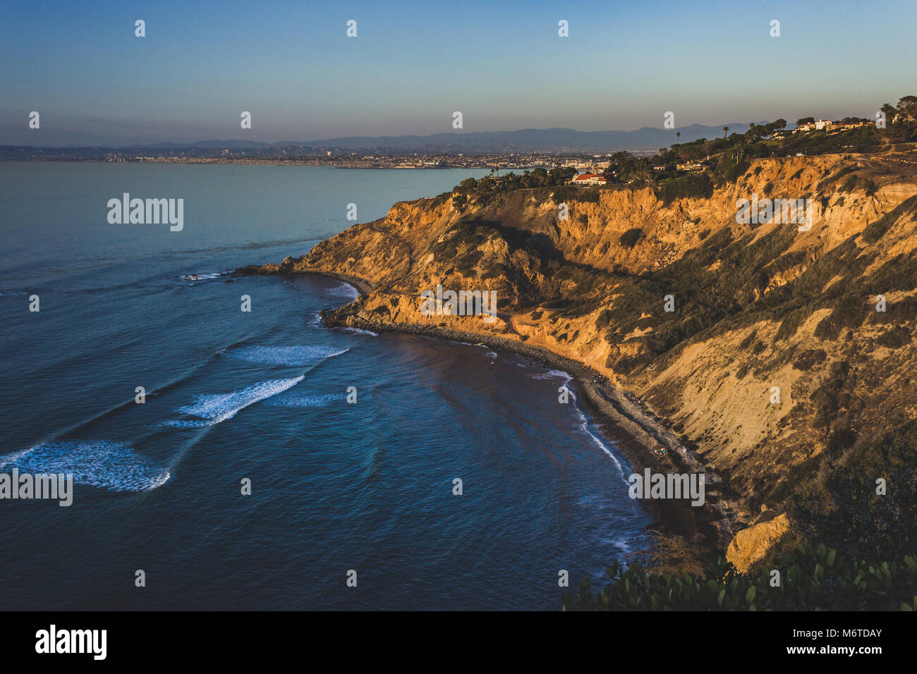 Beautiful view of giant bluffs and homes of Flat Rock Point at sunset with coastline view of nearby South Bay beach - Stock Image