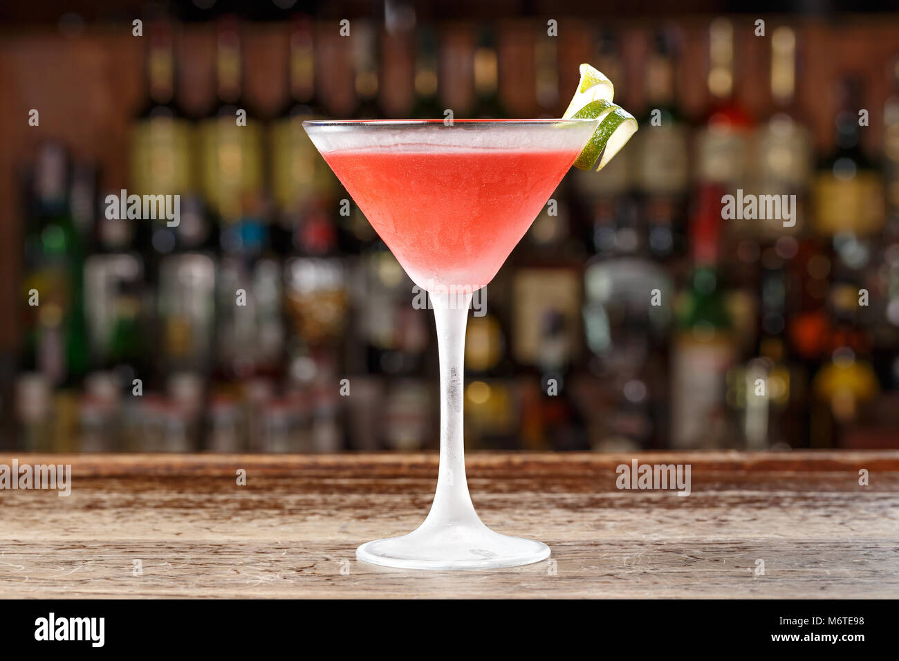 A cosmopolitan alcoholic cocktail is on the bar in a restaurant or in a club. Blurred background of alcohol. - Stock Image