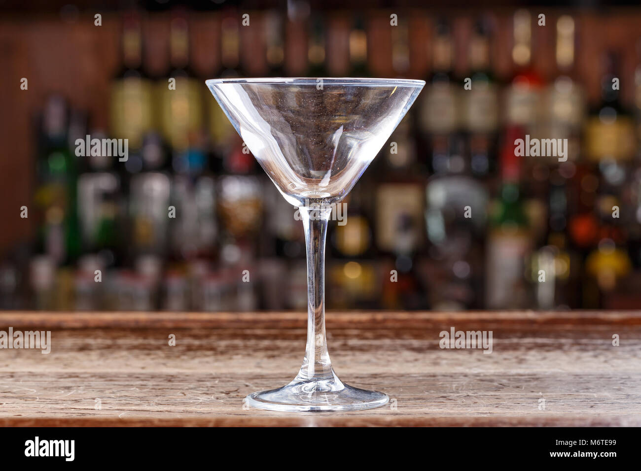 Empty cocktail glass cosmopolitan on the background of the bar, space for text - Stock Image