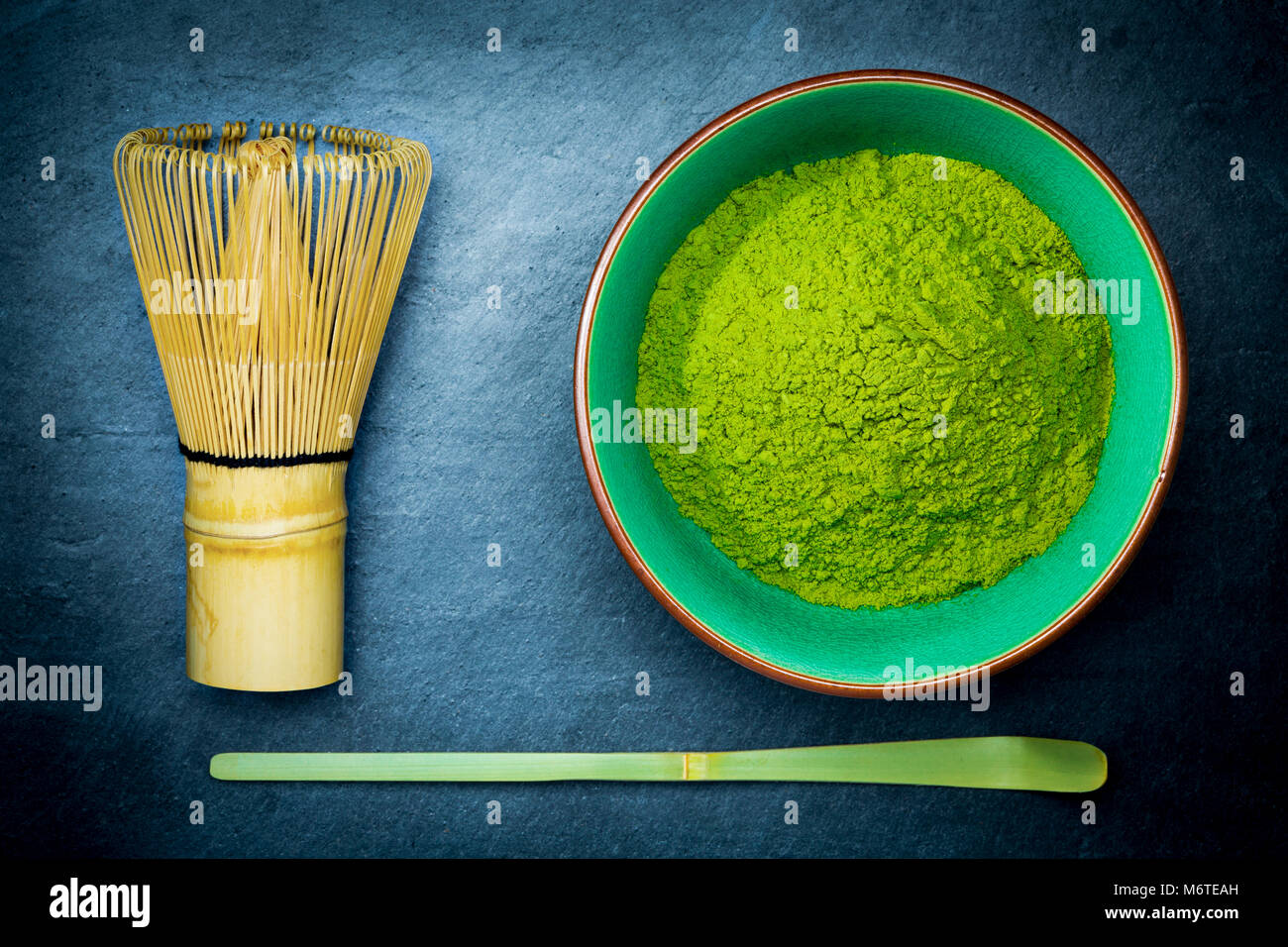 Matcha green tea powder in a bowl with bamboo whisk and spoon on dark slate background. - Stock Image